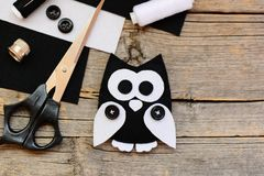 Stuffed felt owl toy, black and white felt sheets, scissors, threads, thimble, black buttons on an wooden background. Things to make with felt sheets. DIY felt Royalty Free Stock Photos