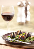 Stuffed figs and rocket with a glass of wine stock image