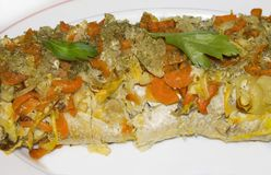 Stuffed fish - pike on a white plate with carrots and onions close -up stock photography