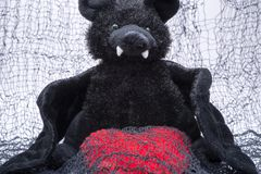 Stuffed funny black bat toy with red fluffy heart on creepy cotton web cloth.