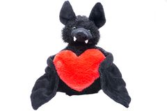 Stuffed funny black bat toy with red fluffy heart on white