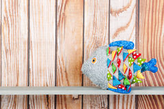 Stuffed funny fish on wooden background Stock Photo