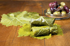 Stuffed Grape Leaves. Traditional stuffed grape leaves with spiced olives and grape leaves on a wooden table Royalty Free Stock Image