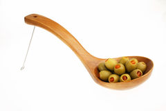 Stuffed green olives. Green olives stuffed with red peppers in a wooden serving spoon Stock Photos