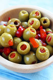 Stuffed Green Olives. A wooden bowl of stuffed pimento green olives royalty free stock images