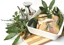 Stuffed guinea fowl. Guinea fowl stuffed with bay leaves in a ceramic baking dish Stock Image