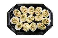 Stuffed Hardboiled Egg. Tasty stuffed hardboiled eggs presented as hors d'oeurvres on a black serving tray Stock Image