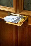 Stuffed letterbox. A brass letterbox in an external door stuffed with mail Stock Images