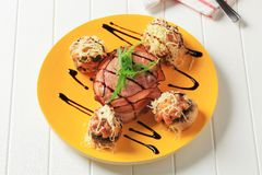 Stuffed mushrooms and bacon-wrapped pork fillet Royalty Free Stock Photography