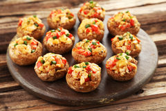 Stuffed mushrooms on cutting board on brown wooden background Stock Photos