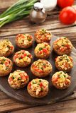 Stuffed mushrooms on cutting board on brown wooden background. Stock Images