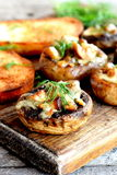 Stuffed mushrooms and fried toasts on a chopping board and wooden table. Baked mushroom caps stuffed with cheese and meat recipe Stock Image