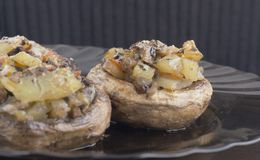 Stuffed mushrooms. On plate with onions and potatoes Royalty Free Stock Image