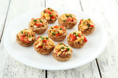 Stuffed mushrooms on plate on white wooden background. Stuffed mushrooms on plate on wooden background Royalty Free Stock Images