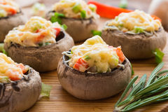 Stuffed mushrooms with vegetables on wooden board Stock Photos