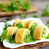 Stuffed omelet rolls with cheese and greens on a white plate. Delicious and light egg sushi recipe. Rustic style. Closeup Royalty Free Stock Image