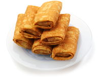 Stuffed pancakes. Stuffed yellow pancakes on the plate over white background Stock Photos