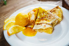 Stuffed pancakes with orange syrup and ice-cream Royalty Free Stock Photos