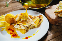 Stuffed pancakes with orange syrup and ice-cream Stock Images