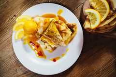 Stuffed pancakes with orange syrup and ice-cream Stock Image