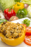 Stuffed pepper with beef and rice. Stuffed bell pepper with beef and rice topped with parmesan cheese and garnished with sliced tomatoes and parsley royalty free stock image