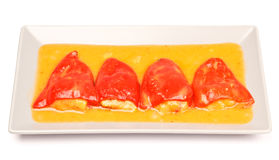 Stuffed peppers. Four red peppers stuffed with seafood and orange sauce. In a grey plate. On white Royalty Free Stock Photo