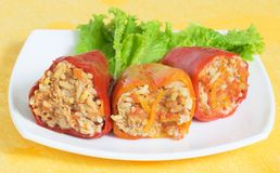 Stuffed peppers. With a lettuce leaf on a white plate, yellow background Stock Photos