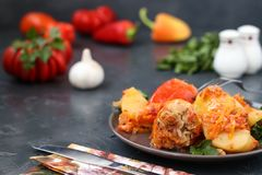 Stuffed peppers with meat, rice and tomato sauce. Located in a plate on a dark background. Multicolored bell pepper stuffed with meat, rice and tomato sauce Stock Images