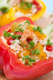 Stuffed peppers with salad of rice and shrimp on a wooden board. Close-up, vertical Stock Photos