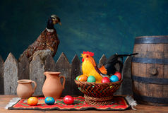 Stuffed pheasant and rooster with colored eggs. On the table Stock Image