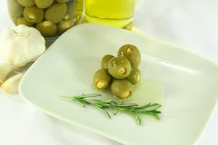 Stuffed pickled Olives in dish with olive oil. Still life picture represent green stuffed with garlic pickled olives in jar and served on dish with olive oil Stock Images