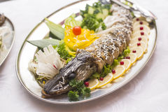 Stuffed pike decorated with vegetables and the greens. Very beautiful restaurant dish Royalty Free Stock Photography