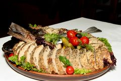 Stuffed pike on a plate of vegetables and leaves of green salad stock image
