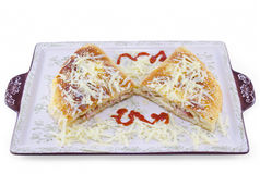 Stuffed pizza cut in half decorated with grated cheese Royalty Free Stock Photo
