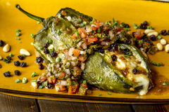 Stuffed Poblano Peppers and Salsa. Close up of roasted Poblano pepper stuffed with melted cheese with fresh salsa royalty free stock photos