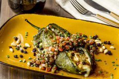 Stuffed Poblano Peppers and Salsa. Fresh roasted Poblano pepper stuffed with melted cheese with fresh salsa garnish with silverware, napkin and glass of wine stock images