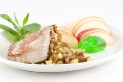 Stuffed Pork chop. Pork loin chop stuffed with toasted rye bread,sauteed onion,celery apples and seasonings, plated with apple slices, mint jelly and a sprig of Royalty Free Stock Images