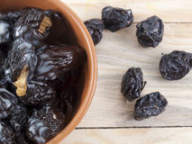 The stuffed prunes on a plate. Prunes on a wooden table are in a plate Royalty Free Stock Photo