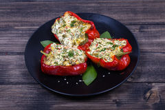 Stuffed red peppers in black plate Stock Photo