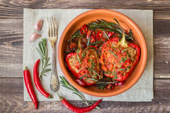 Stuffed red peppers with spicy tomato sauce and rosemary. In clay dish at the rustic wooden background Stock Photography