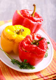 Stuffed red and yellow bell pepper. On plate Stock Photos