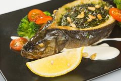 Stuffed seabass on a black plate Royalty Free Stock Photos