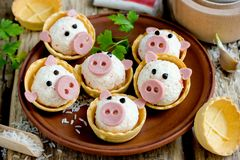 Stuffed snack tartlets in the form of funny pigs. Stuffed snack tartlets with rice, crab sticks, egg, garlic in the form of funny pigs royalty free stock photos
