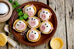 Stuffed snack tartlets in the form of funny pigs. Stuffed snack tartlets with rice, crab sticks, egg, garlic in the form of funny pigs royalty free stock images
