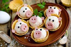 Stuffed snack tartlets with rice shaped funny pigs. Stuffed snack tartlets with rice, crab sticks, egg, garlic in the form of funny pigs stock images