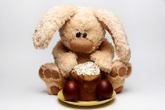 Stuffed soft rabbit with Easter cake and painted eggs on a white background royalty free stock photography