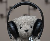 Stuffed Teddy Bear with headphones. Headshot of a brown audiophile teddy bear listening to music through black headphones Royalty Free Stock Images