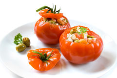 Stuffed tomatoes. Two uncooked stuffed tomatoes on a white dish on white background stock photos