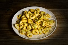 Stuffed tortellini not cooked on the plate - traditional Italian food. Closeup royalty free stock image