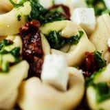 Stuffed tortellini pasta with feta and pesto Stock Image